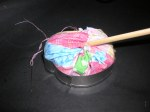 Photo 9: Insert the fabric ball into the cutter and turn the pincushion over.  If needed insert a chopstick into the hole in the gather and push the pot-scrubber into the corners of the cutter.