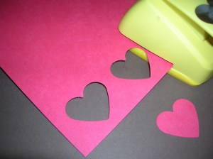 To make a REVERSE PUNCH STRIP, Punch out a row of evenly spaced hearts (make the first punch, then place the puncher edge touching the right edge of the hole and make the second punch, and so on).