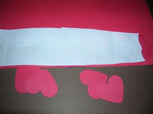 "Apply glue ""around"" the holes and then glue a wrapping paper strip to the paper (design side down so the wrapping paper design shows through the heart shaped holes)."