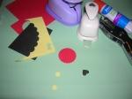 Punch a red 1 inch circle, 1 yellow regular hole punch, and 1 mini black heart punch.