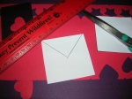 Draw an upside down V on the envelope using a straight edge to create the envelope flap.